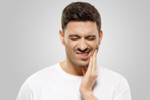 guy holding jaw in pain